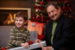 Großvater und Enkel, die zusammen Geschenke einwickeln Stockfotos