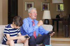 Großvater und Enkel, die zusammen spielen Stockfotografie