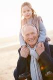 Großvater und Enkelin, die auf Winter-Strand gehen stockbilder
