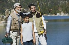 Großvater und zwei Enkel, die Angelruten anhalten Stockfotos