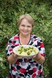 Großvaterfrau mit gekochten Kartoffeln in der Platte Stockfoto