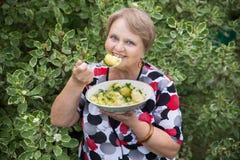 Großvaterfrau mit gekochten Kartoffeln in der Platte Lizenzfreie Stockfotos