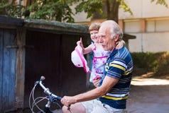 Großvaterreitfahrrad mit Enkelin in den Händen stockfotografie