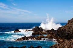 Große zusammenstoßende Welle, die über den Felsen spritzt lizenzfreie stockfotos