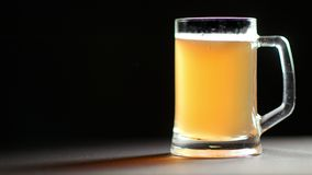 Großer Becher voll Bier-Getränkelangsam Rotation der Erfrischung goldene lokalisiert am schwarzen Studiohintergrund stock footage