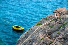 Großer Felsen mit Seil an der Küste stockbilder