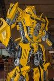 Großer gelber Roboter errichtet mit Autoteilen stockbilder
