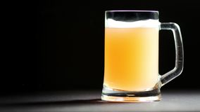 Großer Glasbecher voll Bier mit langsam sich drehen des Schaums lokalisiert am schwarzen Studiohintergrund stock footage