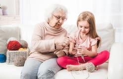 Großmutter unterrichten das Enkelinstricken lizenzfreie stockfotos