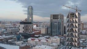 Gro?aufnahme von den unfertigen hohen und modernen Wolkenkratzern bedeckt durch Glas an einem Winterabend gegen den blauen Abend lizenzfreie stockbilder