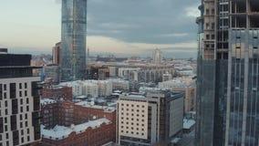 Gro?aufnahme von den unfertigen hohen und modernen Wolkenkratzern bedeckt durch Glas an einem Winterabend gegen den blauen Abend stock video