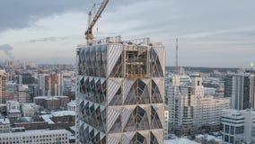 Gro?aufnahme von den unfertigen hohen und modernen Wolkenkratzern bedeckt durch Glas an einem Winterabend gegen den blauen Abend stock video footage