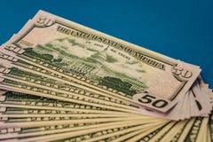 Gro?e fette Geld-Rolle lokalisierte auf einem blauen Hintergrund lizenzfreie stockfotos