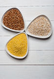 Groats. Barley, buckwheat and millet groats on white wooden table Stock Image