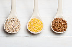 Groats. Barley, buckwheat and millet groats on white wooden table Royalty Free Stock Images
