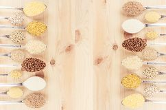 Groats in spoons on beige wood board as decorative background. Top view. Stock Photography