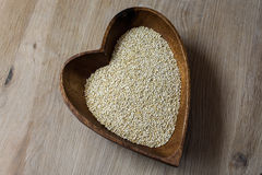 Groats in a wooden bowl. In the shape of a heart on a wooden background Stock Photos