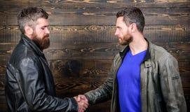 Grobe bärtige Herrenbekleidungslederjacken, die Hände rütteln Freundschaft von groben Kerlen Anerkannte Geschäftsvereinbarung hän stockbild