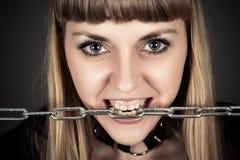 Grobe Frau mit einer Kette in den Zähnen Stockfotos