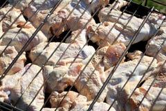 Grobe Hühnerflügel auf einem Grillgitter stockfotografie