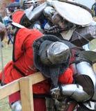 Grobe Ritter kämpfen in der Eisenrüstung mit flügeligen Waffen Stockbilder