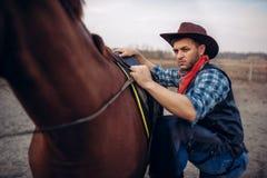 Grober Cowboy klettert zu Pferd auf Texas-Ranch lizenzfreies stockbild