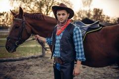 Grober Cowboy wirft mit Pferd, wilder Westen auf stockfoto