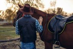 Grober Cowboy wirft mit Pferd, wilder Westen auf stockbild