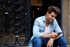 Grober junger Mann, der auf den Schritten sitzen, und Grinsen, wenn eine Mitteilung gelesen wird stockfoto