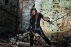 Grober langhaariger Mann mit ledernen Hosen und kühler Gitarre stockfotografie