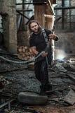Grober langhaariger Mann mit ledernen Hosen und kühler Gitarre lizenzfreie stockfotografie