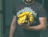 Grober Mann, der ein Bündel Bananen in seinen Händen hält stockbilder