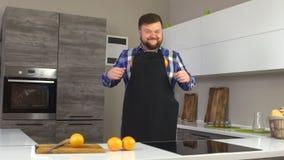 Grober Mann in einem Schutzblech, das herum in einer modernen Küche mit Orangen, Zeitlupe, Vegetarier täuscht stock video footage