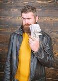 Grober Mann hat Bargeld Reichtum und Wohl Hippie-Abnutzungslederjacke des Mannes grobe b?rtige und Bargeld halten stockbild