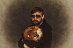 Grober Mann mit einem Bart und moderne Frisur mit einem Hund in ihren Armen Lizenzfreie Stockfotos