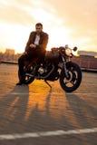 Grober Mann sitzen auf Caférennläufer-Gewohnheitsmotorrad Lizenzfreies Stockfoto