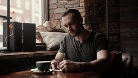 Grober Mann sitzt im Café bei Tisch mit einer Schale und macht Eintritte in einem Tagebuch stock video footage
