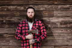 Grober starker Mann mit einem Bart gekleidet in einem überprüften Hemd und heftigen in Jeansständen mit einer Axt in den Händen a lizenzfreies stockfoto