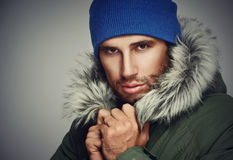 Grobes Gesicht, das ein Mann mit Bart und mit Kapuze Winter sich empört Stockfotografie