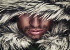 Grobes Gesicht des Mannes mit Bartborsten und mit Kapuze Winter Lizenzfreies Stockfoto