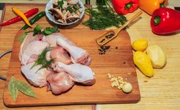 Grobes Hühnerfleisch auf einer Küchentisch-, Gemüse- und Küchenzubehörlüge in der Nähe stockfotografie