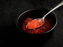 Grobkörniger roter Kaviar im Löffel auf schwarzem Hintergrund Stockbild