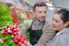 Grocer and customer looking radishes Royalty Free Stock Images