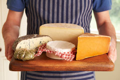 Grocer Holding Board With Selection Of Luxury Cheeses Royalty Free Stock Photography
