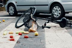 Groceries and broken bike on pedestrian crossing after collision. With a car royalty free stock images