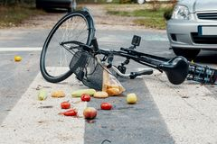 Groceries and broken bike on pedestrian crossing hit by car. Concept photo royalty free stock photo