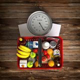 Groceries in a shopping basket on weight scale. Overnutrition, m royalty free illustration
