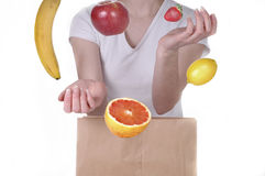 Grocery 3. A woman standing behind a grocery bag and juggling fruit. White background stock photos