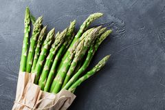 Grocery bag with bunch of fresh green asparagus on stone table top view. Healthy and diet food. Grocery bag with bunch of fresh green asparagus on table top Royalty Free Stock Photos