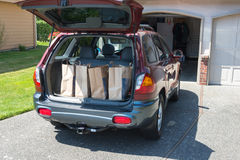 Grocery Bags in Back of Car. Four brown paper bags with groceries in back of car parked in driveway Royalty Free Stock Image